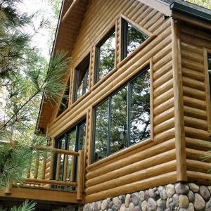 Half log hewn siding with a cedar railing around the deck