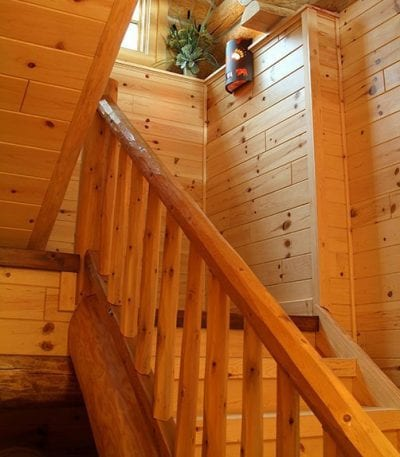 Staircase with cedar railing and knotty pine paneling